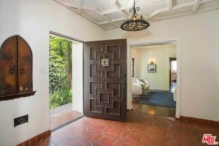 A stylish brown door opens to this entry hall with an arched window and terracotta flooring arranged in a hexagon pattern. It is illuminated by an ornate wrought iron chandelier that hung from the custom ceiling.