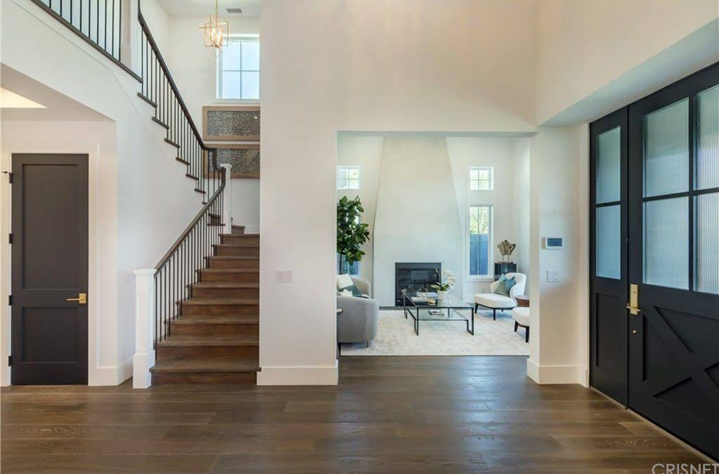 This foyer showcases a large black entry door adjacent to the open doorway that leads to the living room. Next to it is a wooden staircase that's accented with a pair of framed artworks.