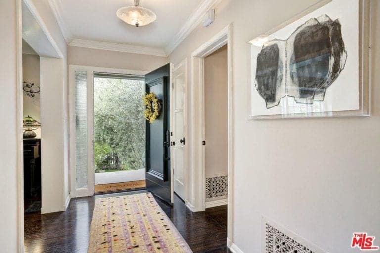 Upon entering, you will be greeted by a charming striped runner that lays on the dark hardwood flooring. This entry hall is decorated with interesting artwork and a yellow wreath mounted on the black front door.