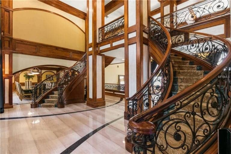 The luxury foyer offers high gloss tiled flooring and an ornate bifurcated staircase topped with beige runners. It is lined with paneled columns that match the wall and ceiling.