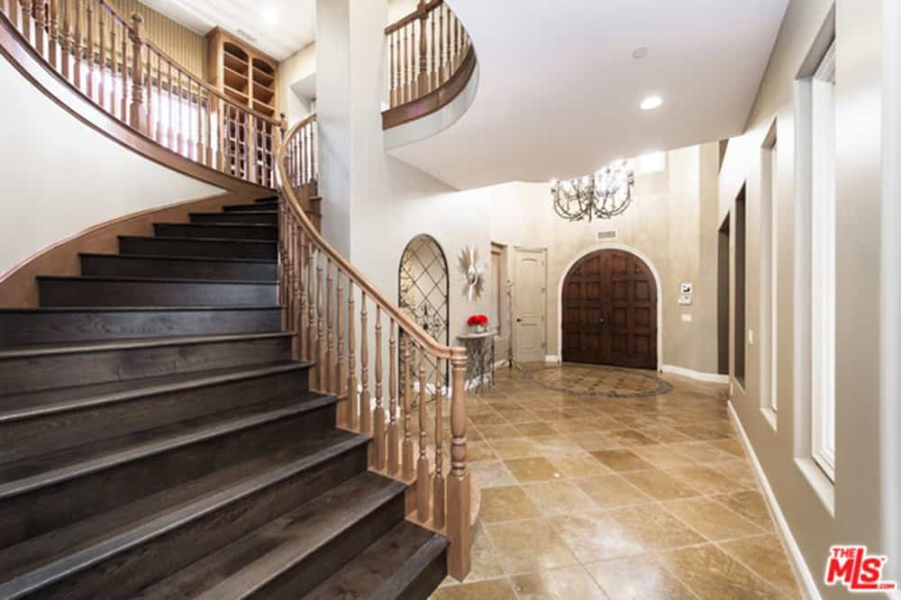 This entry hall offers an arched double door and a winding staircase wrapping around the white column. It is decorated with a grand chandelier and a silver sunburst mirror that hung above a sleek console table.