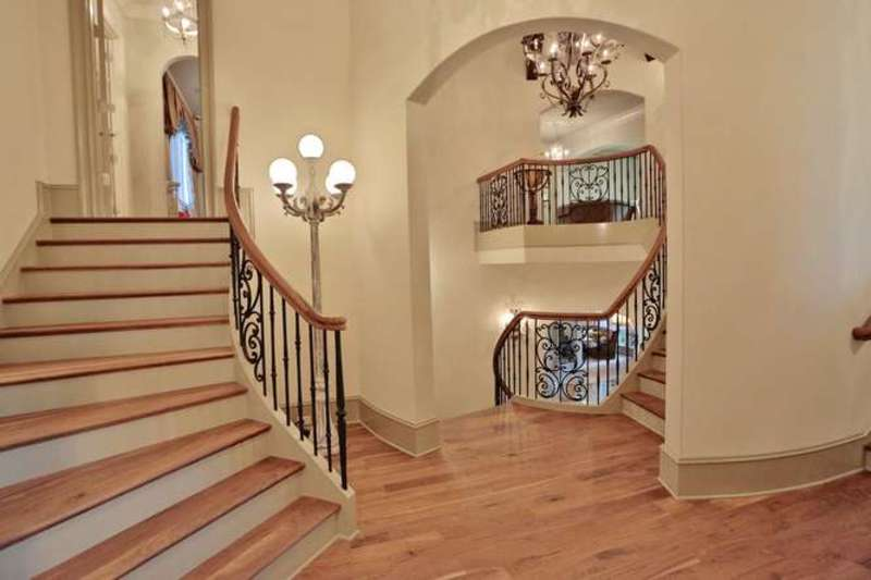 Simple foyer with a unified look featuring a glass globe floor lamp with five heads standing against the curved staircase with wooden treads that match the light hardwood flooring.