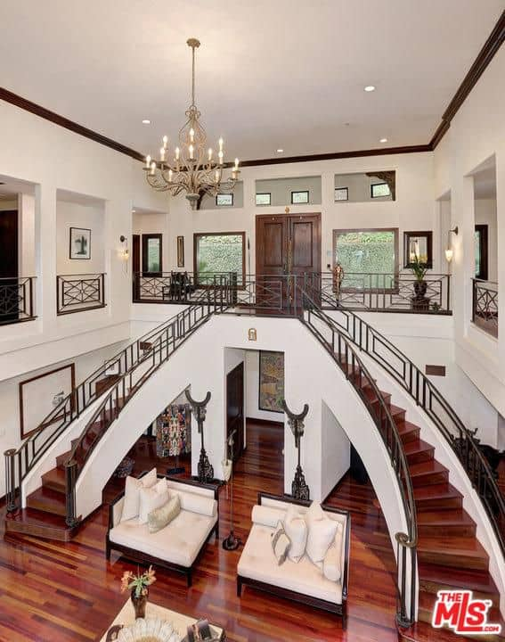 A candle chandelier illuminates this grand entry hall boasting beige cushioned seats and bifurcated staircase with wooden treads blending in with the rich hardwood flooring.
