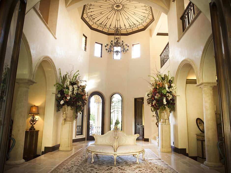 A natural wood French door opens to this grand foyer with an elegant seat over a classic rug flanked by floral pedestals. It is illuminated by a vintage chandelier that hung from the high tray ceiling.