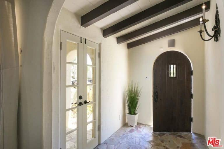 An arched front door opens to this entry hall with flagstone flooring and a shed ceiling lined with dark wood beams. It is lighted by a candle sconce fixed on the white wall.