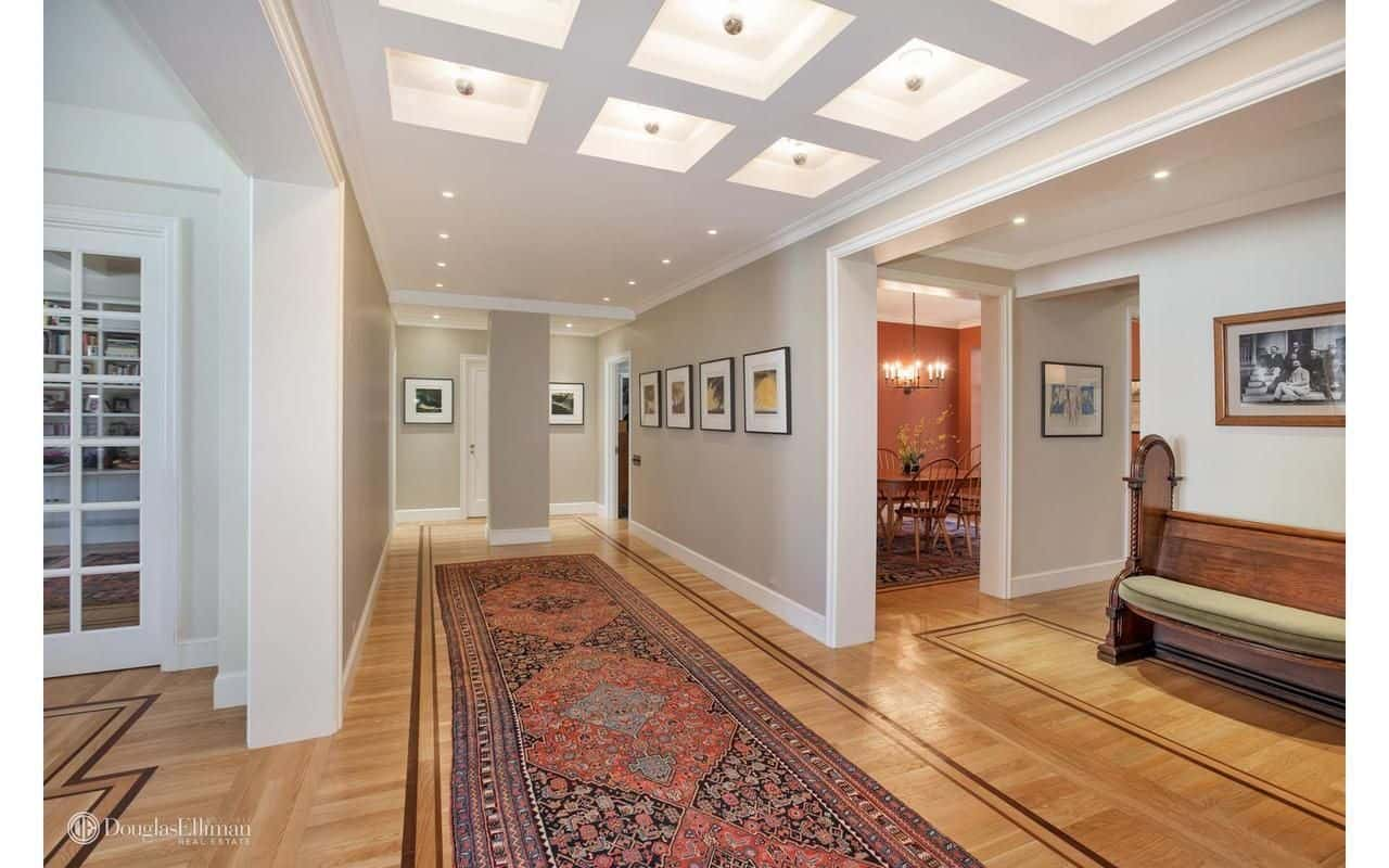 This foyer features a classic patterned runner and a cushioned seat under the wooden framed photo. It opens to a hallway that's accented with gallery frames and illuminated by recessed ceiling lights.