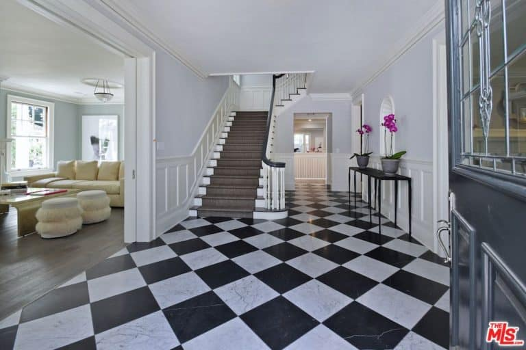Lovely potted flowers on a black console table add a nice accent in this entry hall with marble checkered flooring and a traditional staircase fixed against the white wainscoted walls.