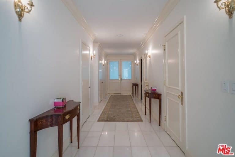Minimalist entry hall with white ceiling and walls accented by brass sconces and knobs. It has wooden console tables and a vintage runner that lays on the tiled flooring.