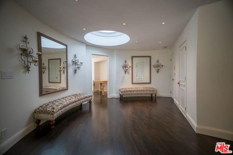 Ornate sconces flanked the wall mirrors that hung above the classy tufted benches over the dark hardwood flooring. It is illuminated by a round skylight along with small recessed ceiling lights.