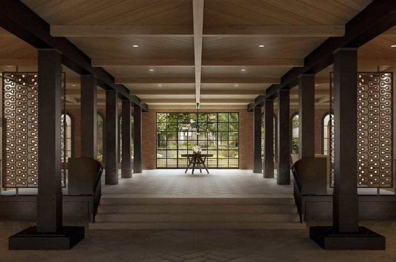 Large foyer with herringbone flooring and concrete stairs leading to a spacious space that's filled with dark wood columns and a round table by the full height glazing.