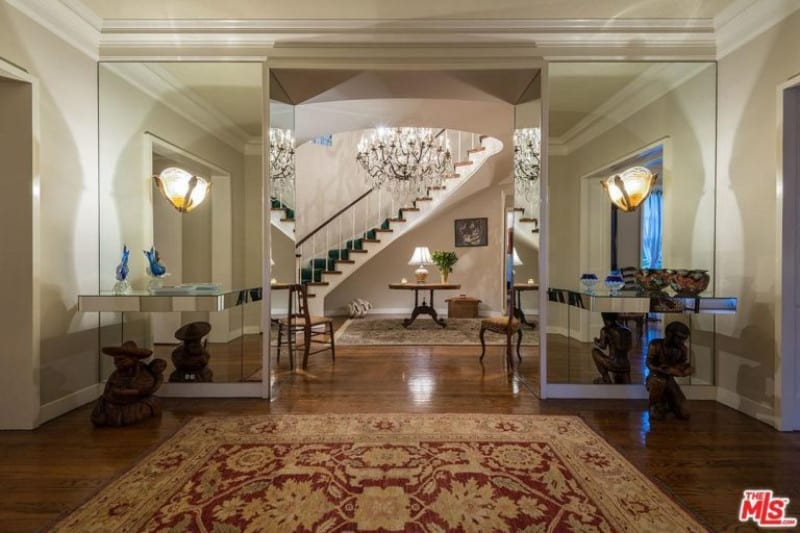 Mirrored walls and a grand chandelier add elegance in this foyer with a curved staircase and classic rugs that lay on the rich hardwood flooring. It includes cozy seats and a round table that's topped with a traditional table lamp.