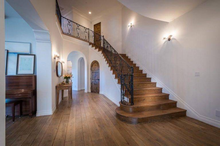 The cozy foyer offers a wooden framed mirror and a rustic console table that blends in with the wide plank flooring. There's a wooden staircase on the side fitted with an arched door that opens to the built-in storage.