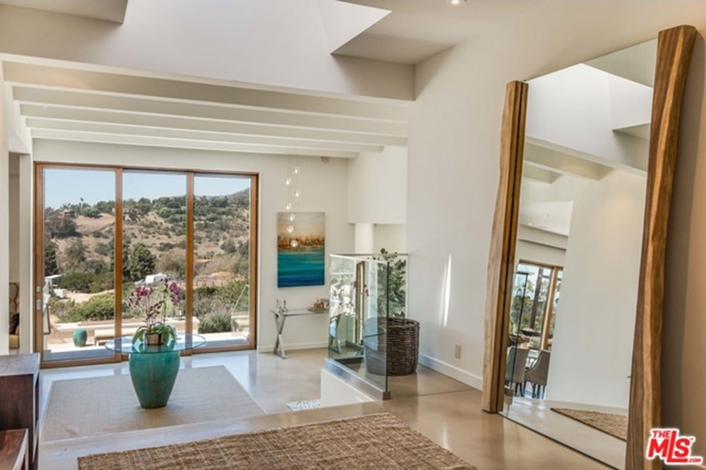 Bright foyer showcases white beamed ceiling and full height windows overlooking the outdoor scenery. It is completed with glass top tables and a full-length mirror that creates a larger visual space in the area.