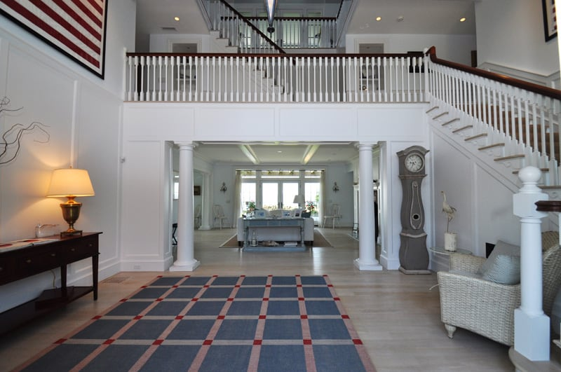 Spacious foyer lined with white columns offers a dark wood console table and a blue checkered rug that lays on the light hardwood flooring. It includes a gray grandfather clock and a wicker chair against the traditional staircase.