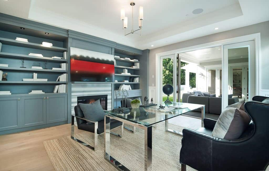 Sleek home office decorated with an abstract painting and a contemporary chandelier that hung over the glass top desk. It is accompanied with black cushioned chairs and a fireplace flanked by built-in cabinets.