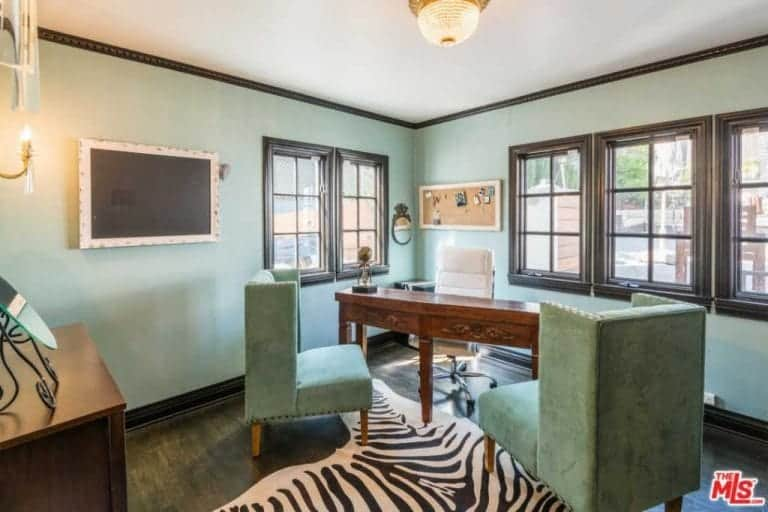 A warm flush mount light illuminates the wooden desk paired with a white swivel chair facing the green velvet wingback chairs that blend in with the mint green walls. It is complemented by a zebra rug that lays on the hardwood flooring.