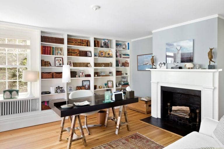 Airy home office boasts a fireplace and a black desk contrasted by a white round back chair. It includes a fireplace and open shelving filled with books and various decors.