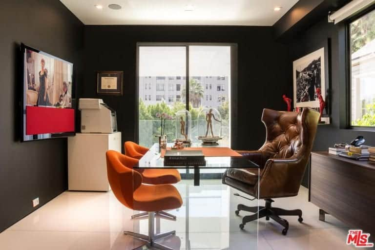 The black home office features a wooden cabinet and a glass desk flanked by a tufted wingback chair and a pair of contemporary orange chairs. It is decorated with black framed artworks along with sculptures inside glass bell jars.
