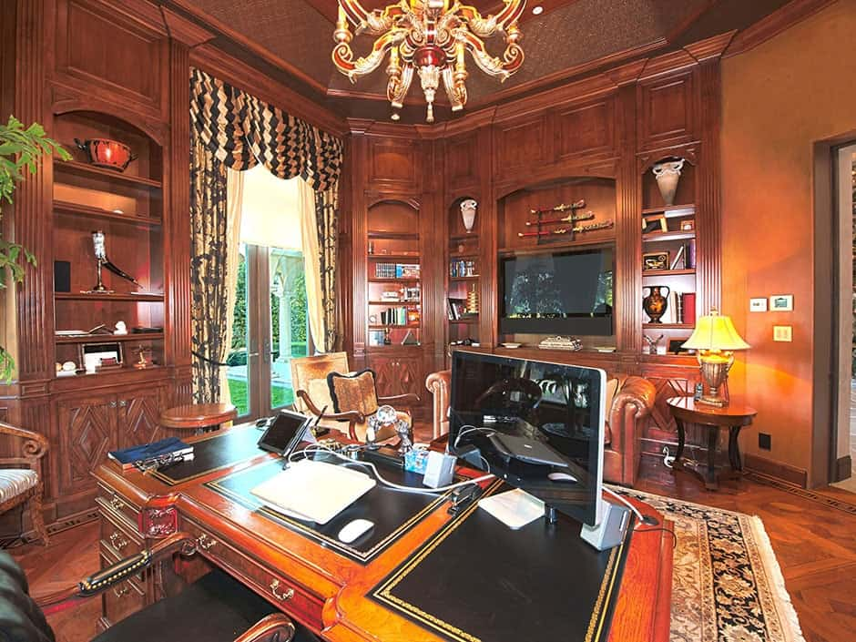 Cozy home office illuminated by a gorgeous chandelier that hung over the wooden desk. It is surrounded by built-in cabinets and a French door that's dressed in classy drapes and valances.