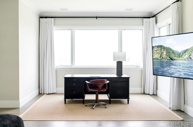 Minimalist home office with a wall mount TV and a dark wood desk paired with a round back swivel chair. It includes glazed windows and a jute area rug that lays on the natural hardwood flooring.