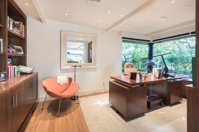 A contemporary coral chair stands out in this white home office with a framed mirror and stylish wooden desk matching with the built-in cabinets. It has a beamed ceiling and glazed windows framing the outdoor greenery.