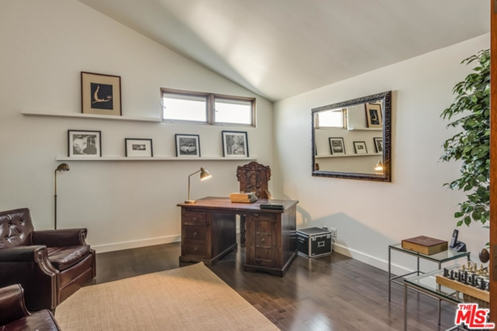 This home office is decorated with a photo gallery and a large framed mirror mounted on the white wall. It showcases leather tufted armchairs and an antique desk paired with a carved wood chair.