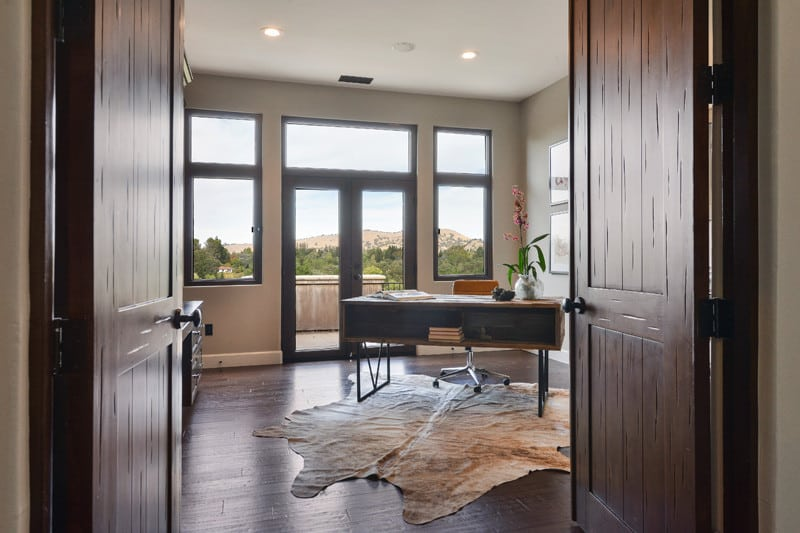A dark wood double door opens to this home office with a metal desk and swivel chair that sit on a cowhide rug over the hardwood flooring. It has glazed windows and doors bringing plenty of natural light in.