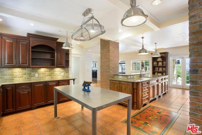 This kitchen offers dark wood cabinetry and a two-tier island by the brick column lighted by chrome dome pendants. It includes a bolted table and a stainless steel pot rack with lights mounted on the beamed ceiling.