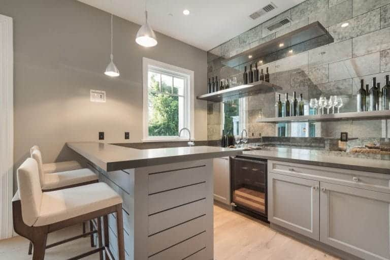 Sleek kitchen with gray cabinets and floating shelves fitted on the mirrored backsplash. It is completed with an L-shaped peninsula that's paired with cushioned counter chairs and chrome dome pendants.