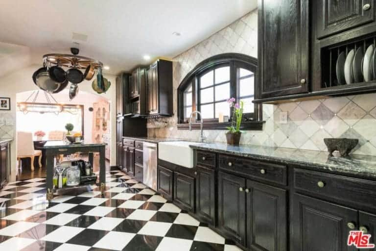 This kitchen offers black cabinetry and a farmhouse sink by the arched window paired with a gooseneck faucet. It includes a round pot holder and dark wood island that sits on a striking checkered flooring.