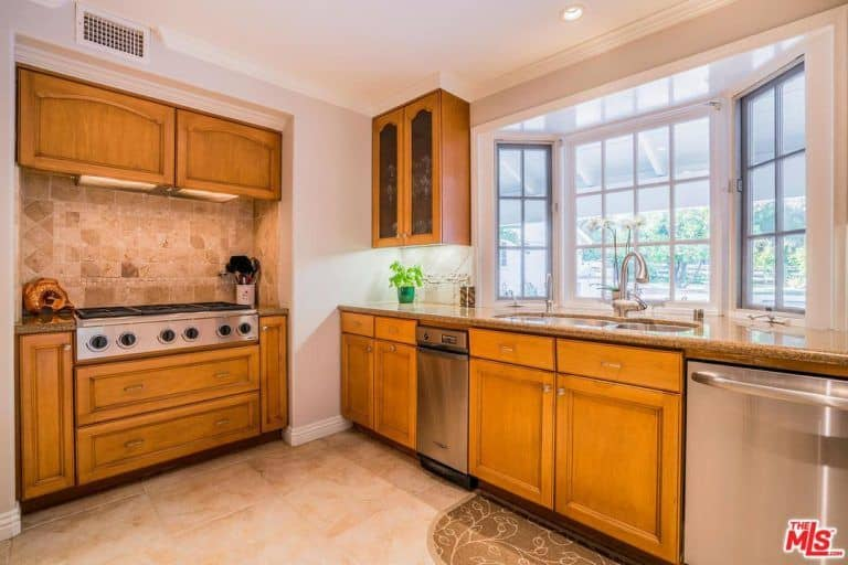 Natural light flows in through the bay window in this bright kitchen with wooden cabinets and granite countertops fitted with dual sink and a cooktop. It includes stainless steel appliances and a lovely floral rug that lays on the beige tiled flooring.