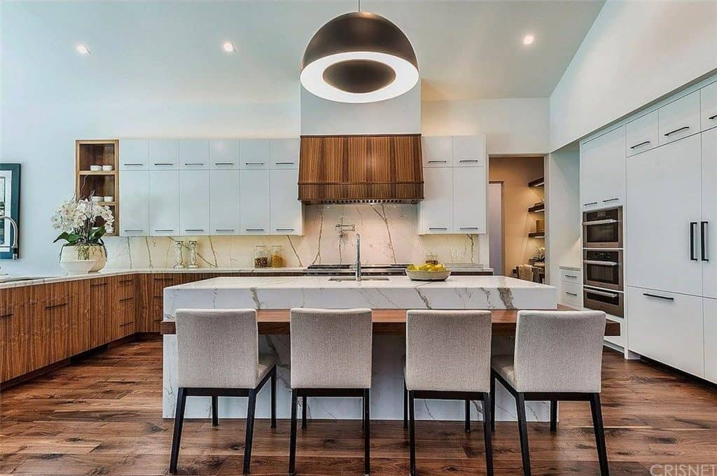 Deluxe kitchen with white and wooden cabinets matching with the range hood that stands out against the white wall and backsplash. There's a marble island in the middle fitted that's complemented with taupe bar chairs and a large black dome pendant.