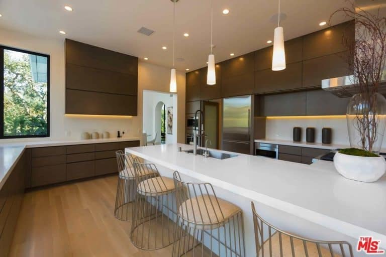 Wooden cabinetry surrounds the white center island with an undermount sink and chrome fixtures. It is lined with lovely glass pendants and metal counter chairs over the light hardwood flooring.