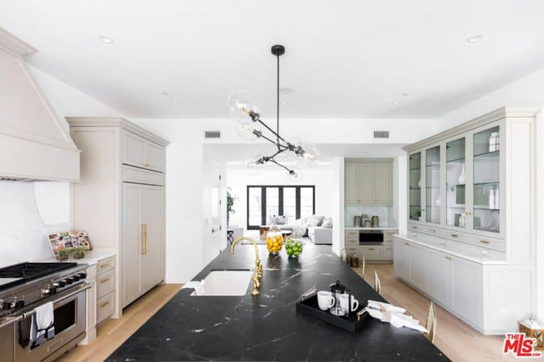 Black marble top island creates a striking contrast to the white cabinets that are accented with brass hardware. It is illuminated by a contemporary chandelier that hung from the regular white ceiling.
