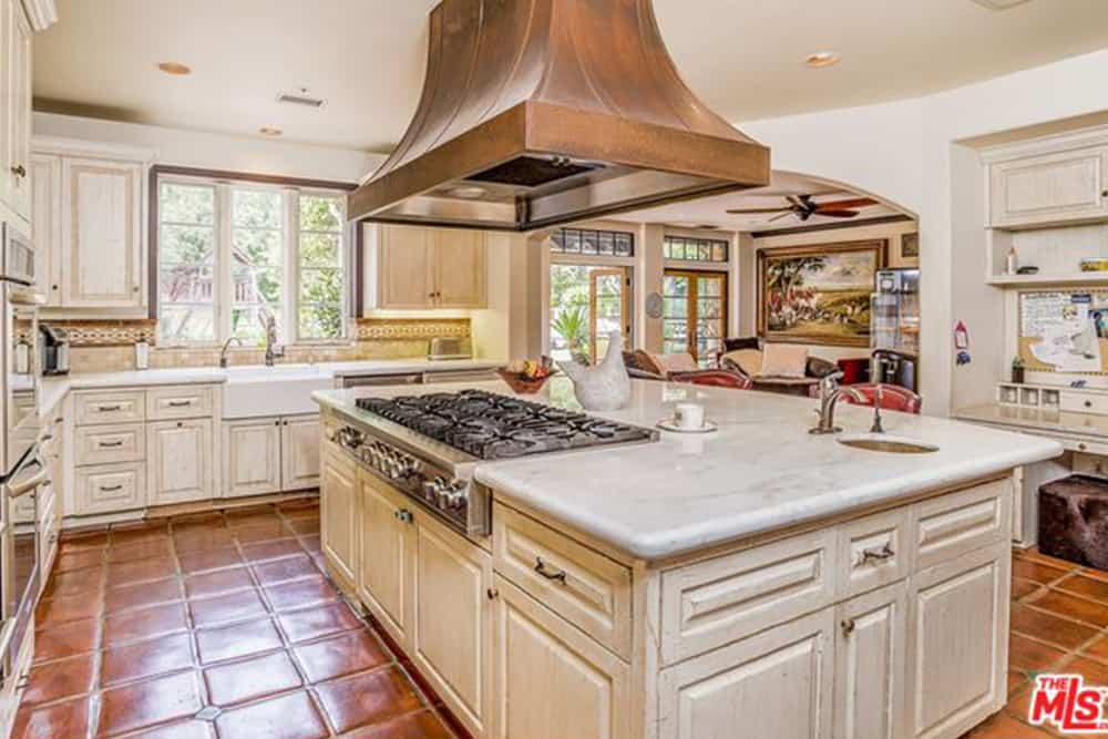 A copper vent hood stands over a marble top island that's fitted with a round sink and built-in cooktop. It is surrounded by inset appliances and distressed white cabinetry along with an open archway leading to the dining area.
