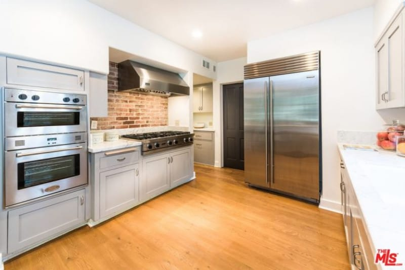 Red brick backsplash adds texture in this kitchen with stainless steel appliances and light gray cabinetry fixed against the white walls. Natural hardwood flooring adds warmth to this area.
