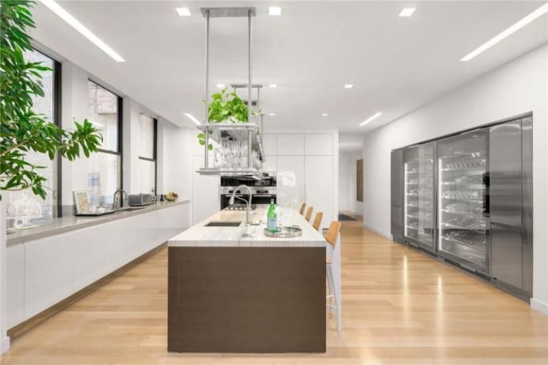 Well-lit kitchen showcases stainless steel appliances and sleek white cabinetry fading into the white walls. There's a central island in the middle with wooden counter chairs and floating wine glass racks overhead.