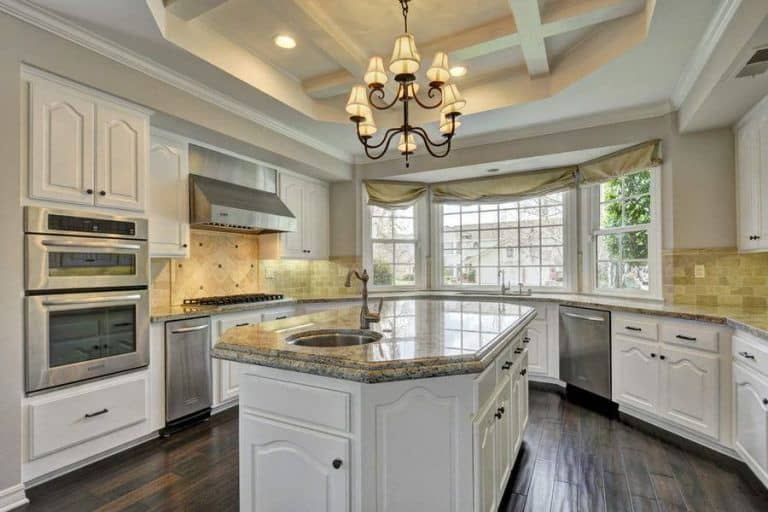 White kitchen with inset appliances and a granite top island fitted with a round sink and chrome faucet. It is illuminated by a wrought iron chandelier and recessed lights mounted on the tray ceiling.