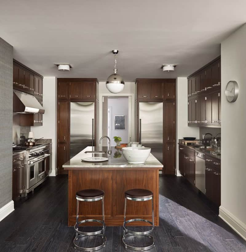 A pair of inset refrigerators and round chrome stools create symmetry in this kitchen with wooden cabinetry and a matching center island lighted by a glass globe pendant.