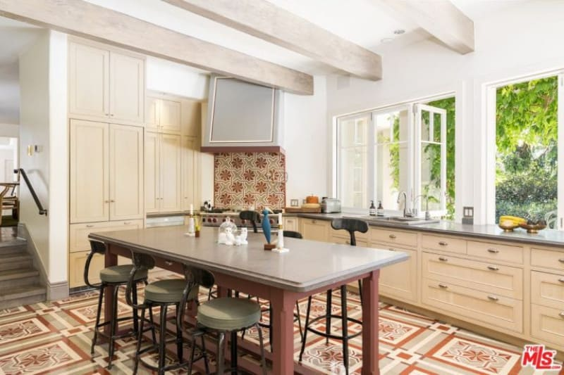Natural light flows in through the white framed windows in this kitchen with cream cabinets and a central island surrounded by stylish cushioned chairs. It has patterned flooring and a regular white ceiling lined with light wood beams.
