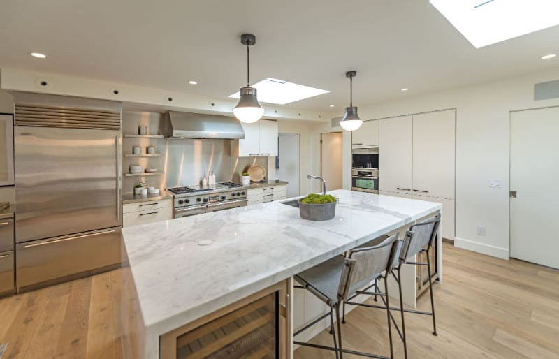 Modern kitchen with stainless steel appliances and white cabinetry matching with the marble top island that's paired with metal counter chairs. It has wide plank flooring and a regular white ceiling fitted with a pair of glass pendants and skylights.
