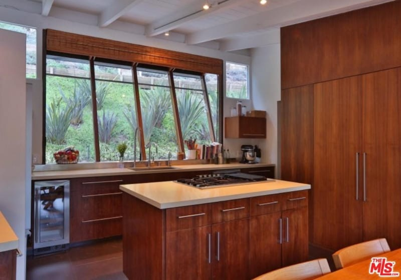Small kitchen with white beamed ceiling and glass paneled windows overlooking the outdoor greenery. It includes inset appliances and wooden cabinetry matching with the central island that blends in with the hardwood flooring.