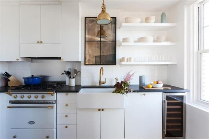 The bright kitchen boasts white cabinets and cooking range accented with brass hardware. It is equipped with a built-in wine fridge and a farmhouse sink that's paired with a gold gooseneck faucet.