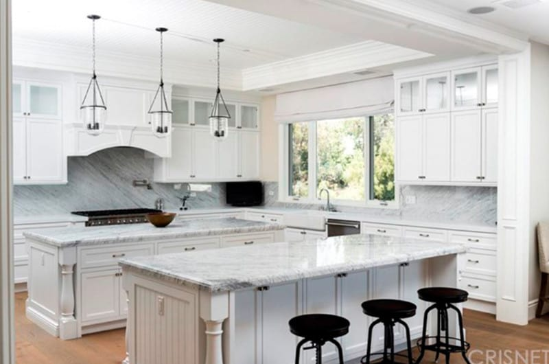 Black round bar stools add a sleek contrast to the white cabinetry and islands that are topped with marble countertops. It is illuminated by glass pendant lights that hung from the tray ceiling.