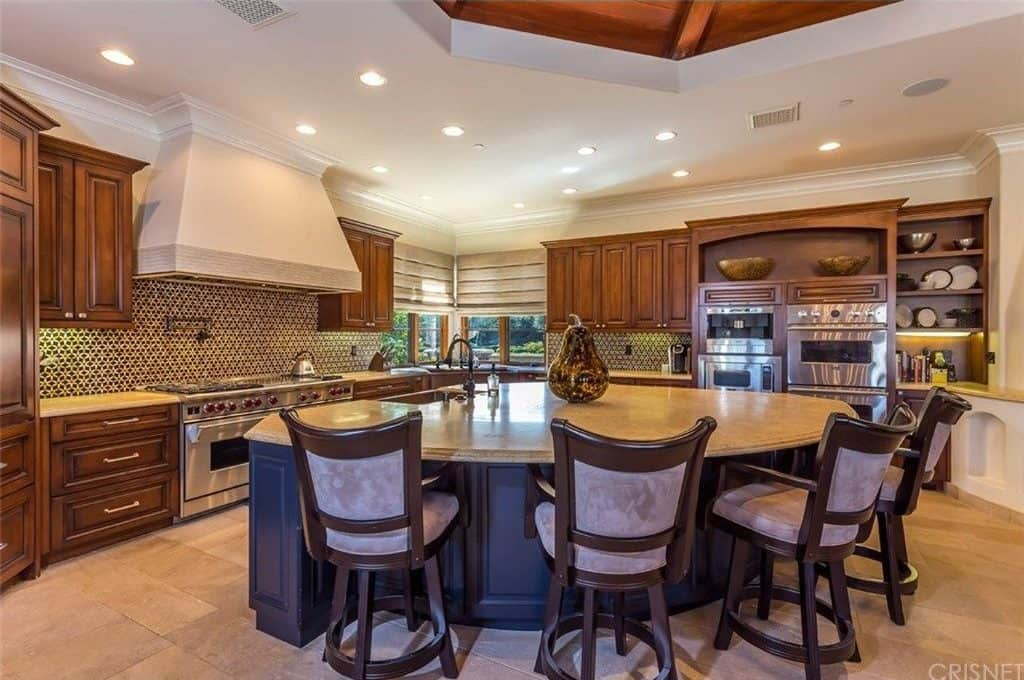 Wooden cabinetry adds a striking contrast to the gray island that's surrounded by velvet cushioned chairs. This kitchen has beige tiled flooring and corner windows covered in cream roman shades.