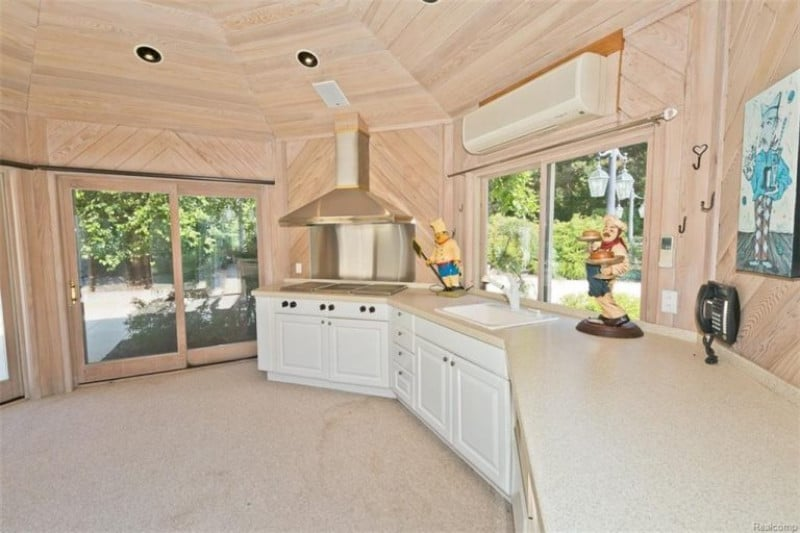 This kitchen is decorated with chef sculptures and an artwork that's mounted on the wood paneled wall. It has white cabinets and a granite countertop fitted with an undermount sink and a built-in cooktop.