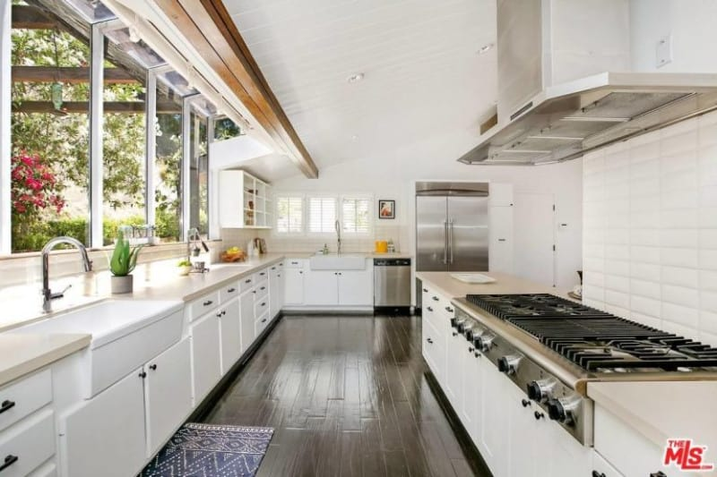 Galley kitchen with glass paneled windows and a dark hardwood flooring topped by a blue patterned rug. It is equipped with stainless steel appliances and farmhouse sinks that blend in with the white cabinets.