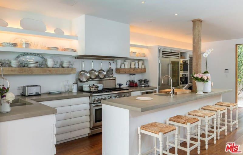 White bar stools sit at a granite top island that's supported by a rustic column. It is accompanied by stainless steel appliances and floating shelves along with white cabinets that blend in with the walls.