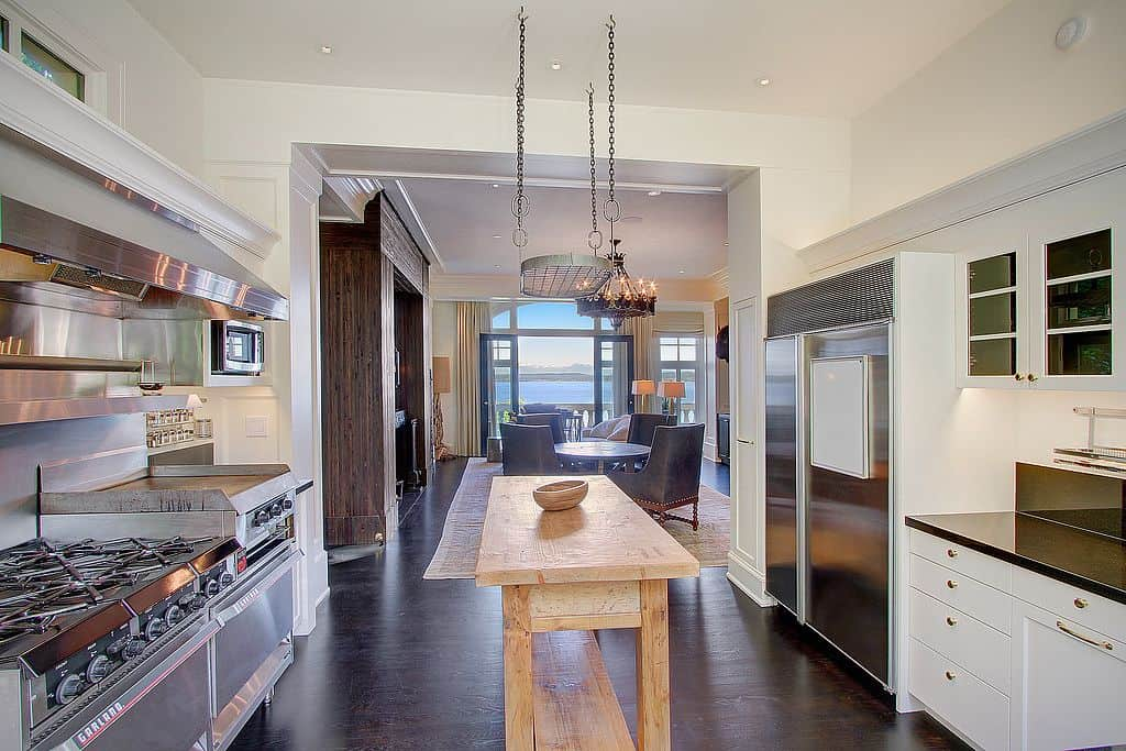 A stainless steel pot rack hangs over the wooden island that's topped with a matching decorative bowl. It sits in between the stainless steel appliances and white cabinetry accented with gold hardware.