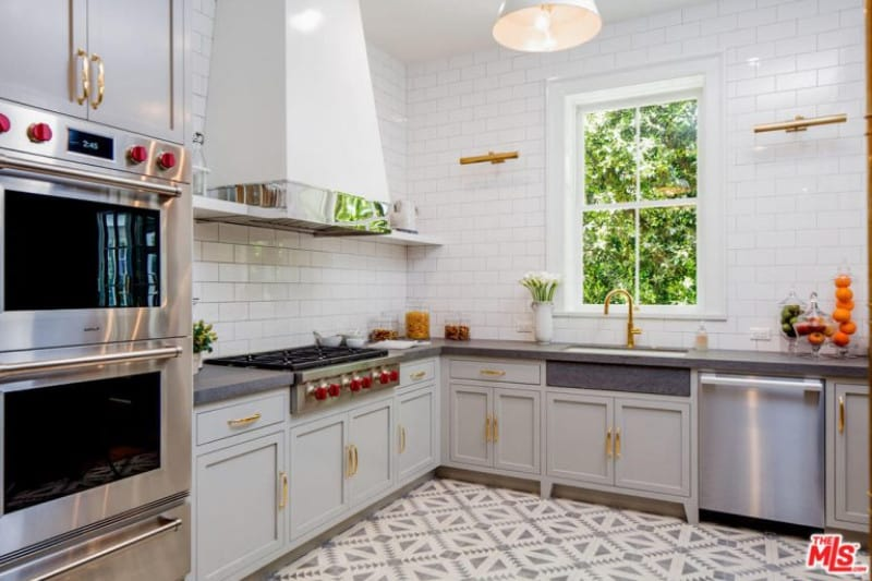 Patterned flooring adds a striking accent in this kitchen with stainless steel appliances and white cabinets fitted with brass pulls. It includes a dome pendant light and a white vent hood with chrome trim fixed against the subway tile backsplash.